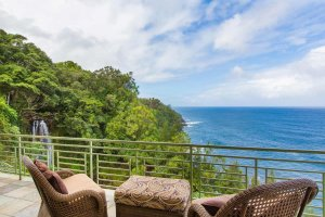 A sitting area on a balcony overlooking a waterfall and the ocean