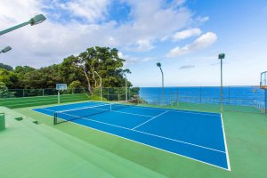 A tennis and basketball court overlooking the ocean
