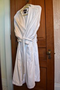 white robe hanging on door