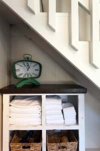 nook under the stairs with towels and clock