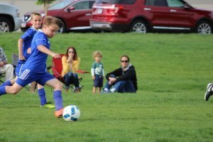Shooters Soccer Club Facility boy kicking soccer ball families watching