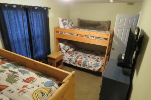Two bunk beds in a room with closed blue curtains