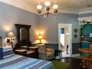 Chandelier hanging over bed and vanity in bedroom