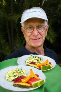 man holding plates of fruit and omelets