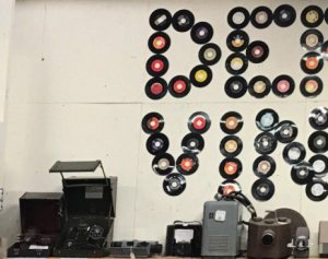 records on wall along with various antique items