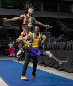 A man supporting two other men in a gymnastic feat