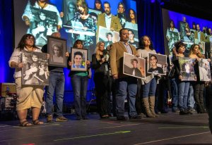 A stage full of people holding photos of lost loved ones