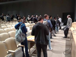 People gathered at the front of an auditorium to speak to Kenley McAvoy