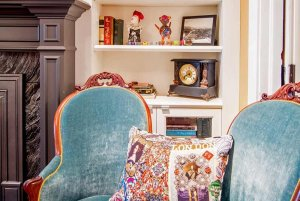 plush chairs and decora and painting of seafoamted shelves