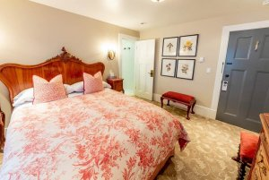 bed with pink floral bedspread and headboard