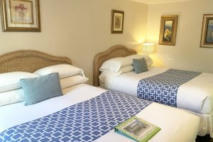 two queen beds with blue pillows and blankets