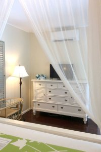 foot of bed with view of white dresser with tv