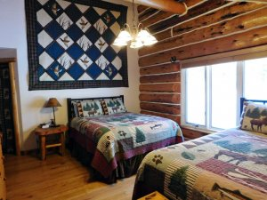 double room with quilt wall hanging