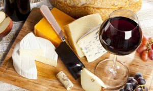 A glass of wine and an assortment of cheese
