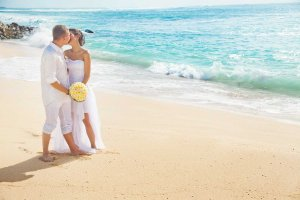 Couple kissing and holding a bouquet on a beach