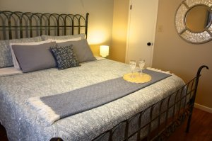 bed with blue spread and wine tray