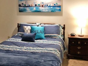 Bed with Pillow Saying Relax