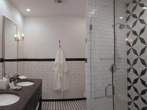 Bathroom with Walk in shower, two sinks, and a bathrobe
