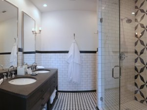 Bathroom with two sinks, walk in shower, and bathrobe