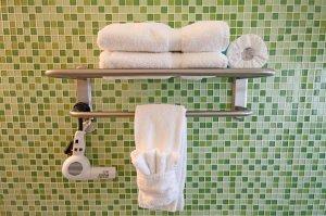 towel rack on green tile wall