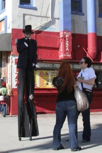 people talking to man on stilts