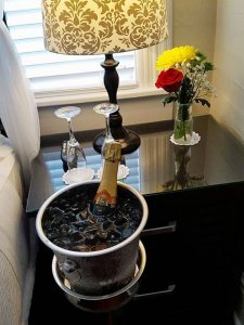 champagne in ice bucket next to bed