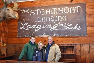 Innkeepers in Front of Sign Saying Steamboat Landing Lodging on the Lake
