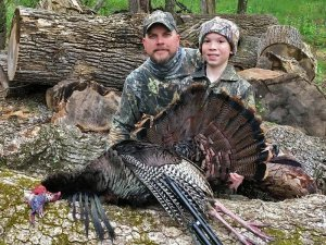 Father and son with harvested turkey