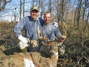 Two hunters displaying a harvested trophy buck