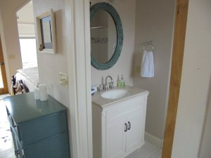 bathroom sink and blue-framed mirror