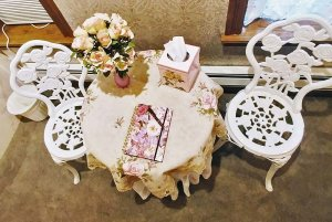 white iron chairs near side table with flowers