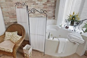 wicker chair near dressing curtain and bathtub