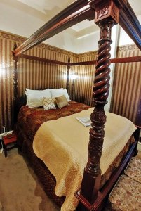 intricately carved wooden four-poster bed