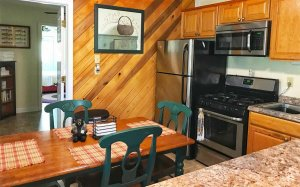 A kitchen with stove, fridge, microwave, and sink as well as a table and chairs