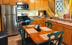 A table with four chairs near kitchen appliances