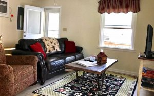 Sitting area with couch and armchair around coffee table and television