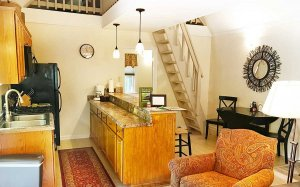 Kitchenette, table and chairs, and steep ladder-style stairway