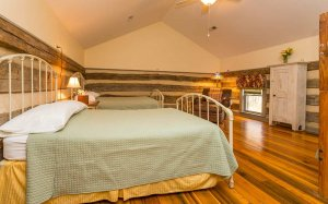 Two beds in a room with rustic wooden walls