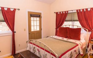 A bed with floral covers in a red themed cottage
