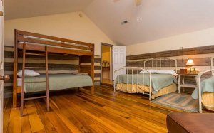A bunk bed and two other beds in a room with rustic wooden walls