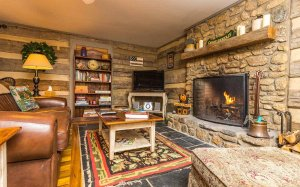 A sitting area with large fireplace, television, and board games