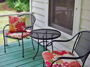 A small table with two chairs with red cushions on a porch