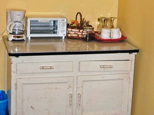A small cabinet with various kitchen amenities on top