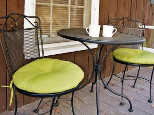 A small table with two chairs with green cushions on a porch