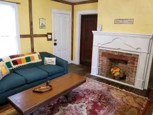 A couch and coffee table near decorative fireplace