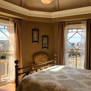 Bed next to windows in bedroom