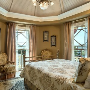 Windows and bed in dome ceiling bedroom