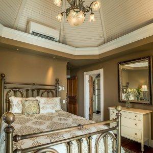 Bed next to dresser under mirror