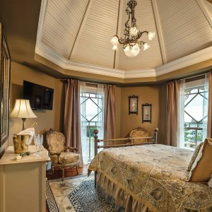 Queen-sized bed facing window and wall-mounted television