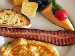 Bacon, fruit, and omelette on plate